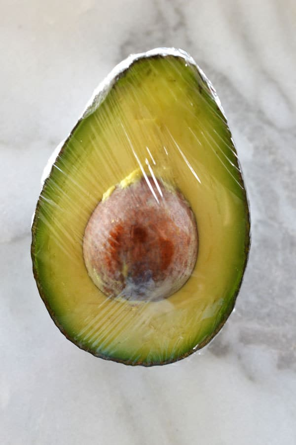 half an avocado wrapped in plastic wrap