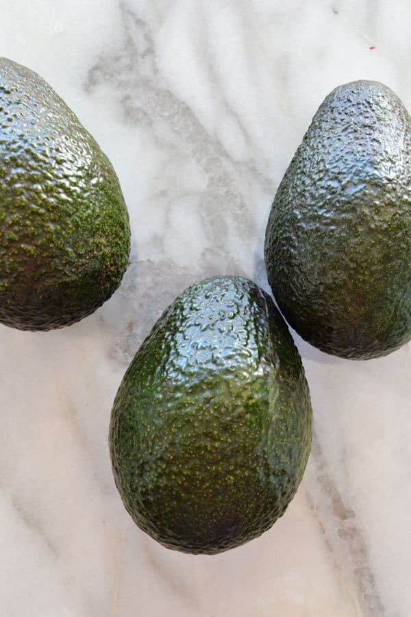 3 avocados stored on the counter