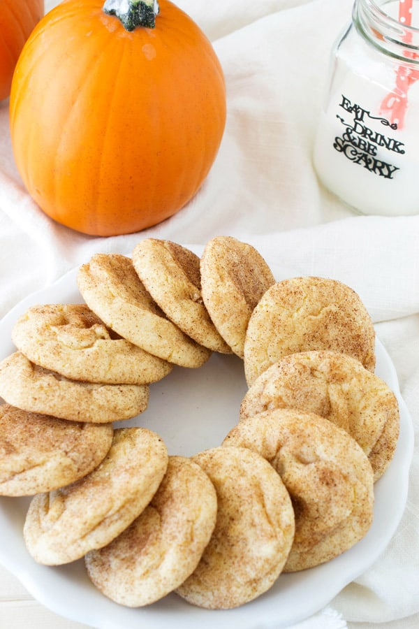 plate of pumpkin snickerdoodles with pumpkin and milk in the background