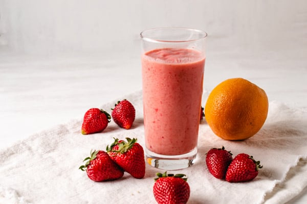glass of strawberry smoothie surrounded by strawberries and an orange