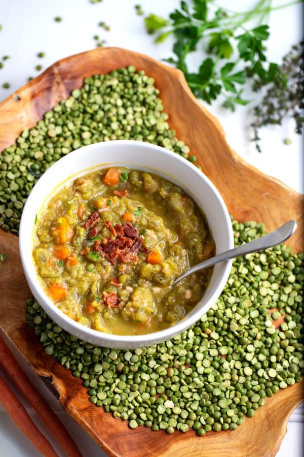 bowl of split pea soup surrounded by dry split peas and fresh herbs