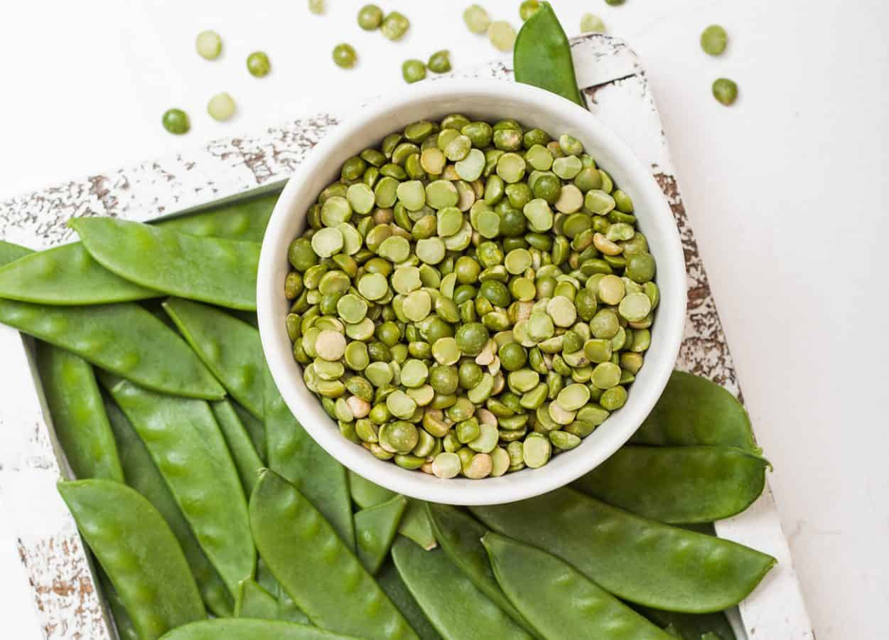 bowl of split peas surrounded by pea pods