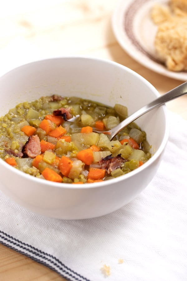 bowl of split pea soup with spoon and plate with biscuit