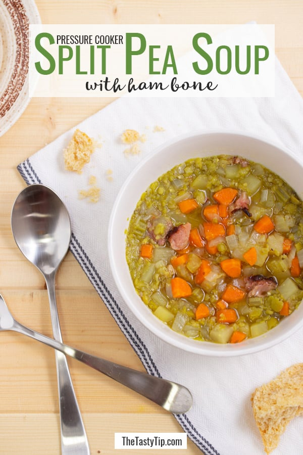 bowl of split pea soup with spoons and roll on the side