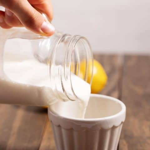 pouring buttermilk into a cup