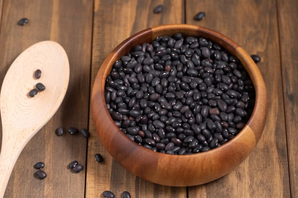 bowl of raw black beans and wooden spoon