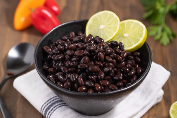 closeup of cooked black beans with lime slices