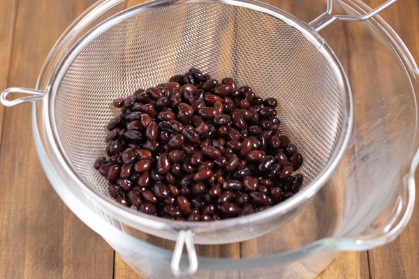 cooked black beans in a strainer