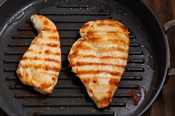 2 pieces of cooked chicken in grill pan
