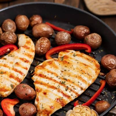 cooked chicken breast in grill pan with potatoes and red peppers