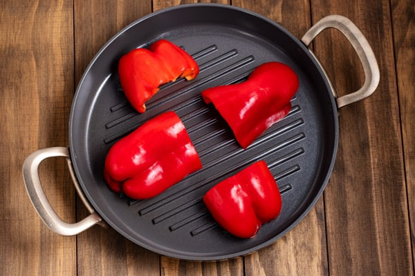 halved red peppers on a grill pan ready to be roasted