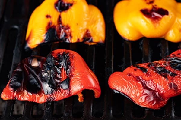 halved bell peppers on the grill after being roasted