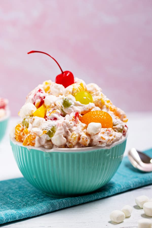 big bowl of ambrosia salad with a cherry on top