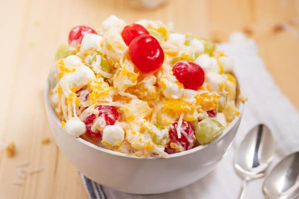 bowl of ambrosia salad with cherries on top