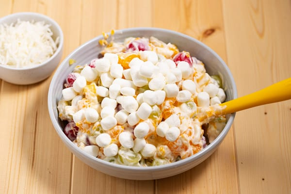 mixing marshmallows in fruit salad with whipped cream and sour cream