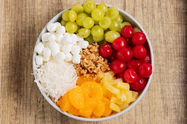 bowl of fruit, marshmallows, coconut, and walnuts