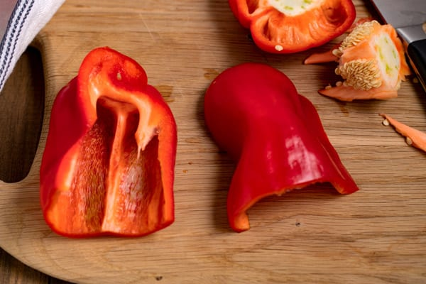 red peppers cut in half on a cutting board