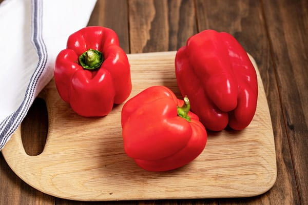 3 red bell peppers on a cutting board