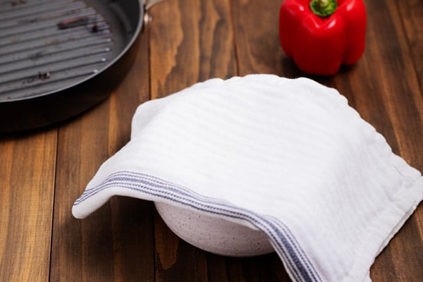 towel covering bowl with roasted peppers in it