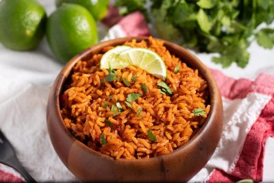bowl of seasoned rice on napkin with lime wedges and snips of cilantro