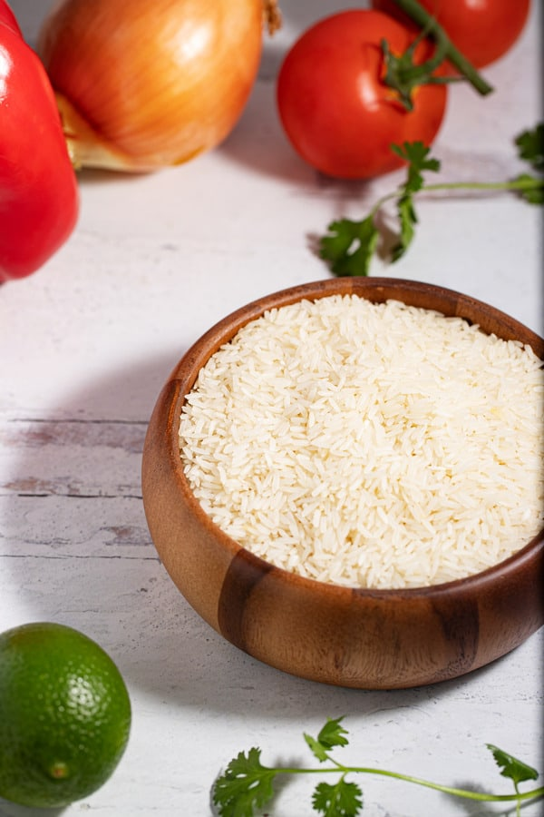 bowl of raw white rice surrounded by lime, cilantro, tomatoes, onion, and red bell pepper