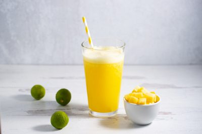 glass of aguas frescas next to cup of pineapple and 3 limes