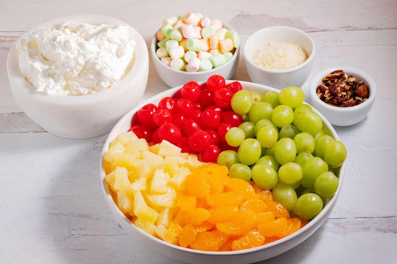 ingredients of ambrosia salad: mandarin oranges, pineapple, grapes, maraschino cherries, creamy sauce, marshmallows, coconut, and pecans