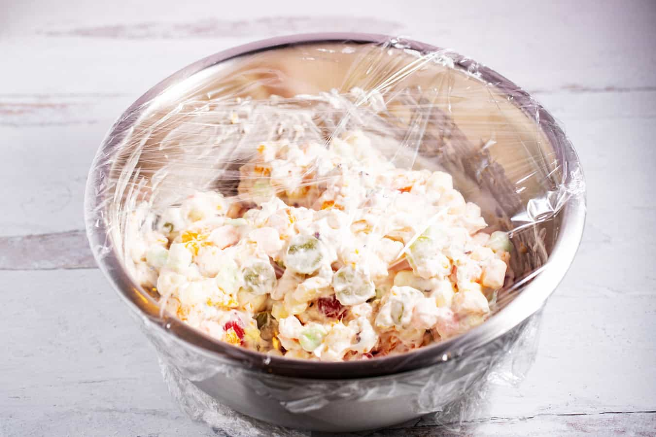 ambrosia salad covered in plastic wrap ready to go in the refrigerator