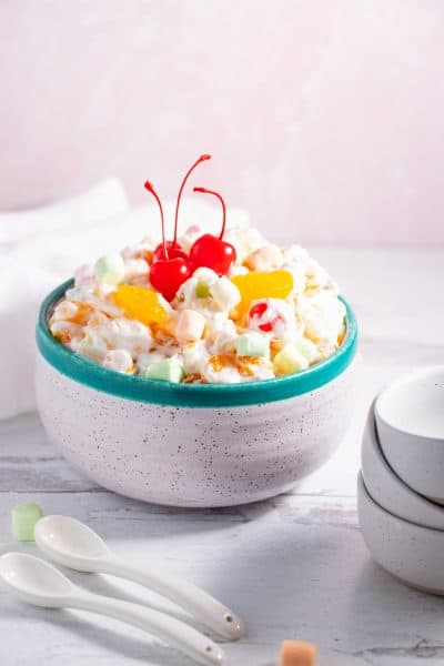 bowl of ambrosia salad set out with serving dishes