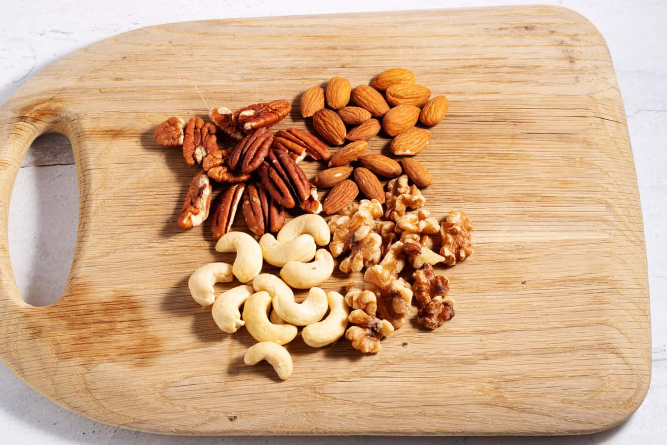 piles of pecans, almonds, walnuts, and cashews