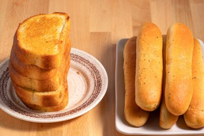 plate of Texas toast and plate of breadsticks