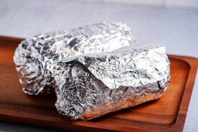 2 burritos wrapped in aluminum foil