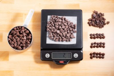 measuring cup of chocolate chips, chocolate chips on a kitchen scale, and chocolate chips lined up