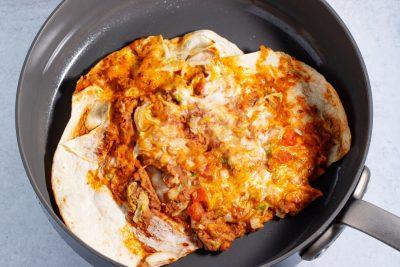 open burrito reheating on the stove